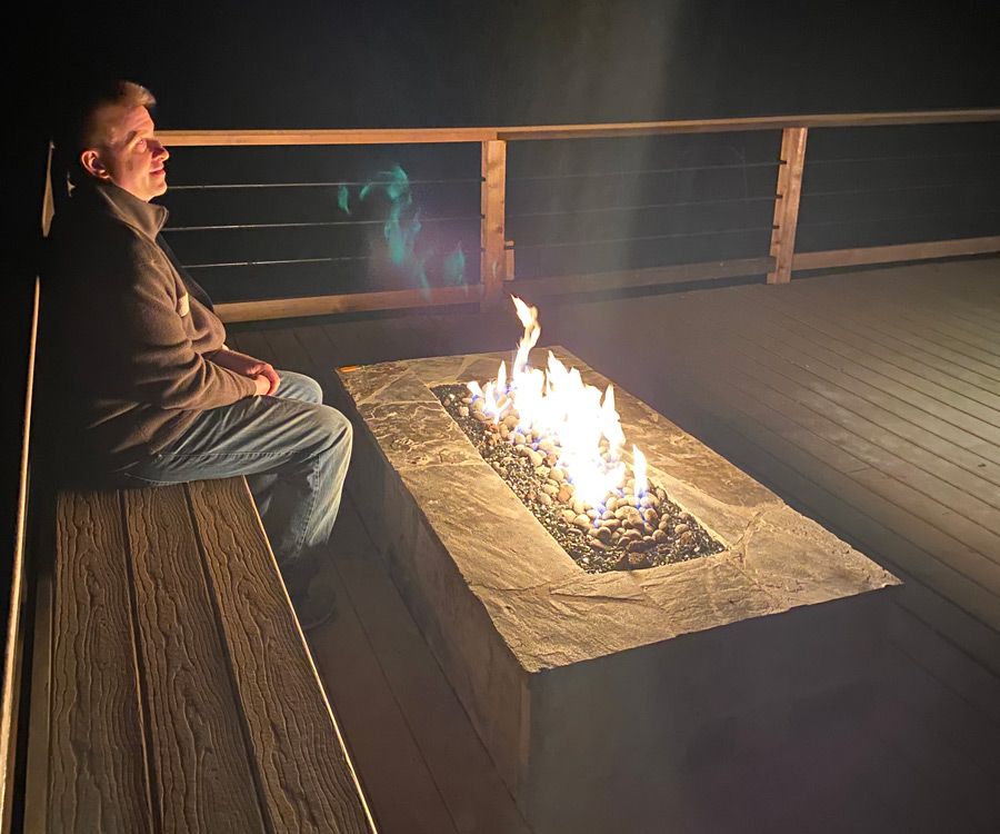 man warming beside the fire pit in glow