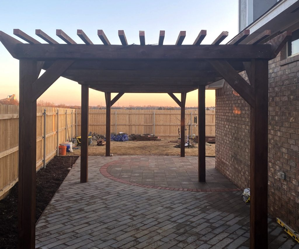 a hand built pergola on the side of a house